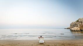 Der Mann, der hinten auf einem Wagenaufenthaltsraum auf dem Strand liegt Mann und Meer Lizenzfreie Stockbilder