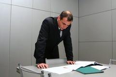 Der Mann hinter einer Tabelle mit Dokumenten Lizenzfreies Stockfoto