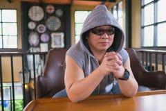 Der Mann im Anorak im Pochen und in der Hip-Hop-Art sitzt auf Sofa Seitenansicht betend lizenzfreie stockfotos