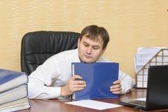 Der Mann im Büro, das einen Ordner mit Dokumenten hält Lizenzfreies Stockbild