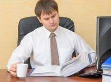 Der Mann im Büro mit einer Schale, die Ordner mit Dokumenten hält Lizenzfreie Stockfotografie