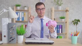 Der Mann, der im B?ro sitzt und wirft eine M?nze in das Sparschwein, welches die Kamera betrachtet und zeigt sich seinen Finger stock footage