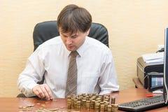 Der Mann im Büro am Tisch glaubt Münzen und addiert sie Spalten lizenzfreie stockbilder