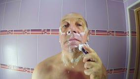 Der Mann im Badezimmer rasiert die Stoppel von seinen Backen und von Kinn mit einem Rasiermesser stock video
