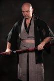Der Mann im Bild eines Samurais mit Klinge in der Hand Stockfotografie