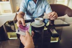 Der Mann, der im Café sitzt, gibt einem anderen Mann Geld stockbild