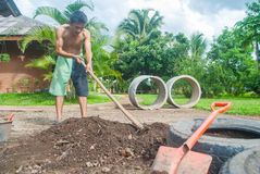 Der Mann, der im Garten mithilfe eines Schaufelgrabens arbeitet Stockfotografie