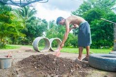 Der Mann, der im Garten mithilfe eines Schaufelgrabens arbeitet Lizenzfreies Stockbild