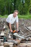 Der Mann im Holz sägt einen Baum eine Kettensäge Lizenzfreie Stockbilder