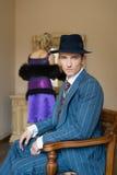 Der Mann im Hut sitzt auf einem Stuhl und der Frau, die am Spiegel stehen Lizenzfreies Stockbild