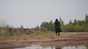 Der Mann im Regenmantel und im Hut gehend durch die Wüste findet etwas aus den Grund stock footage