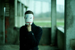 Der Mann im Schwarzen in einem verlassenen Gebäude in der Maske lizenzfreie stockbilder
