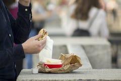 Der Mann isst einen Schnellimbiß auf der Straße stockfoto