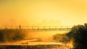 Der Mann ist auf der Brücke in einem orange Nebel über dem Fluss Lizenzfreie Stockfotos