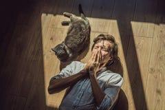 Der Mann ist zu einer Katze allergisch Ein Mann niest wegen der Tatsache, die nahe bei einem Haustier stockfotografie