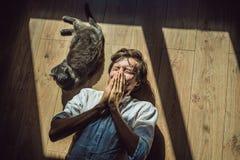 Der Mann ist zu einer Katze allergisch Ein Mann niest wegen der Tatsache, die nahe bei einer Haustier FAHNE, LANGES FORMAT stockfotos