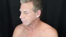 Der Mann, der an jede Seite als Bentonit-Gesichtsmaske sich wendet, trocknet stock footage