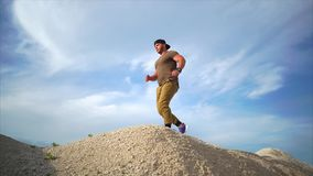 Der Mann läuft, der Athlet läuft entlang den Sandhügel und springt über Hindernisse stock video