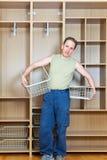 Der Mann legt Körbe in einer neuen Garderobe fest stockbilder