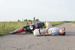 Der Mann liegt auf dem Asphalt nahe dem Motorrad, das Thema von Verkehrsunfällen lizenzfreies stockfoto