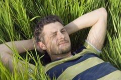 Der Mann liegt auf einem Gras Lizenzfreie Stockfotos