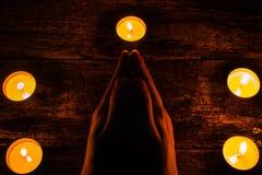Der Mann liest ein Gebet umgeben durch Kerzen Lizenzfreie Stockbilder