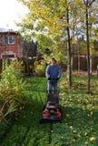 Der Mann mäht einen Rasen Stockbild