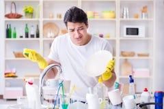 Der Mann, der am Müssen Teller waschen frustriert ist stockfotos