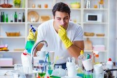 Der Mann, der am Müssen Teller waschen frustriert ist stockfoto