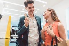 Der Mann müssend mit Kreditkarte für Modeeinzelteile zahlen seine Frau kaufte Lizenzfreie Stockfotos