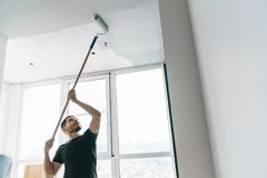 Der Mann malt die Wände und die Decke im Grau auf seinem Balkon in der Hintergrundbeleuchtung Stockfoto