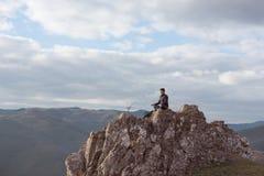 Der Mann meditiert in der Natur nach einem Weg in den Hügeln im Gewinn Lizenzfreie Stockfotografie
