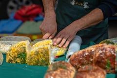 Der Mann mit dem Messer schneidet den Käsemarkt auf dem Tisch Lizenzfreie Stockfotos