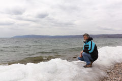 Der Mann mit einem Bart, der auf der Bank des Sees sitzt Stockfotos