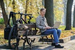 Der Mann mit einem Laptop stockbilder