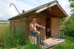 Der Mann mit einem nackten Torso sitzt über ein ländliches Bad Stockfotografie