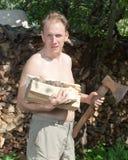Der Mann mit einer aufspaltenaxt bereitet Brennholz vor, um das Haus zu erhitzen Stockbild