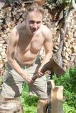 Der Mann mit einer aufspaltenaxt bereitet Brennholz vor Stockfotografie