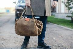 Der Mann mit einer Tasche geht zu einem Mantel zum Haus Stockfotografie
