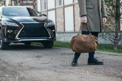 Der Mann mit einer Tasche geht zu einem Mantel zum Haus Lizenzfreie Stockbilder