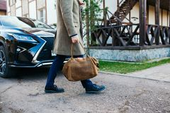 Der Mann mit einer Tasche geht zu einem Mantel zum Haus Stockfoto