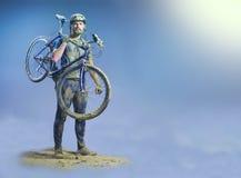 Der Mann mit Fahrrad im Sand, der auf abstraktem Hintergrund steht collage Stockfotos