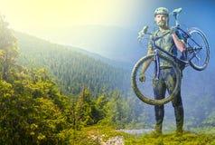 Der Mann mit Fahrrad im Sand, der auf Gebirgshintergrund steht collage Stockfoto
