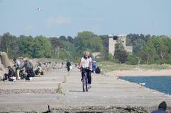 Der Mann mit Fahrrad ist auf dem Nordwellenbrecher in Liepaja, Lettland Lizenzfreies Stockfoto