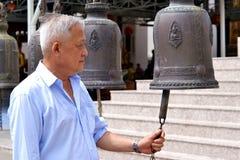 Der Mann mit großer Glocke im Tempel stockfoto