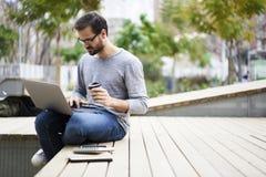 Der Mann mit Handy Kaffee genießend konzentrierte sich auf Aufgabe unter Verwendung des Laptop-Computer und Radioapparates 5G Ver Lizenzfreie Stockfotografie