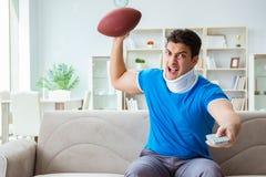 Der Mann mit Nackenverletzung amerikanischen Fußball zu Hause aufpassend stockbilder