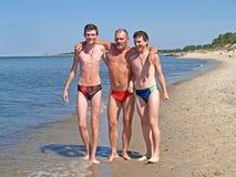 Der Mann mit Söhnen auf der Bank der Ostsee Lizenzfreies Stockbild