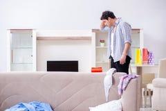 Der Mann mit Verwirrung zu Hause nach Hausparty stockbilder