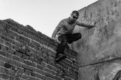 Der Mann nimmt an parkour auf dem Dach des Hauses teil lizenzfreie stockfotografie